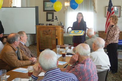 Debra Smith of Sunbelt Ford and Dr. Babs Thomas, Superintendent of the Worth County Board of Education present the local Kiwanis Club with a cake before leading the group in singing Happy Birthday, as the local club celebrated its 90th anniversary last Wednesday.