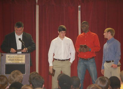 Head Coach Scotty Ward recognizes the 2012 football captains at last week's awards banquet. The team leaders include Eli Reddell, Marlon Hall, and John Buchanan. (not pictured: Lavonte Robinson)
