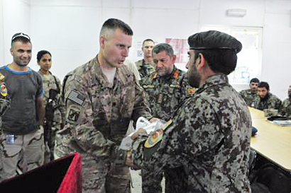 U.S. Army Lt. Col. Michael Acord, Deputy Commanding Officer for 4th Brigade Combat Team, 10th Mountain Division, presents certificate to Sgt. Maj. Khiraz Gull, the 201st Corps surgeon senior enlisted advisor, during the Corps' first combat medic graduation at Forward Operating Base Gamberi, July 21, 2013.