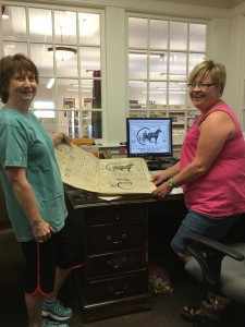 Lynn Fowler (left) holds a bound version of the 1909 edition of The Sylvester Local and Leigh Wiley (right) shows the digitized version on her computer.